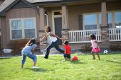 Mother and children running and playing in front yard