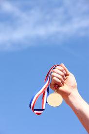 stock photo of gold medal  - Hand holding gold medal - JPG