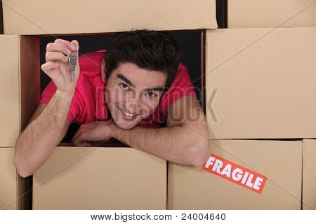 portrait of young man amid removal boxes holding key
