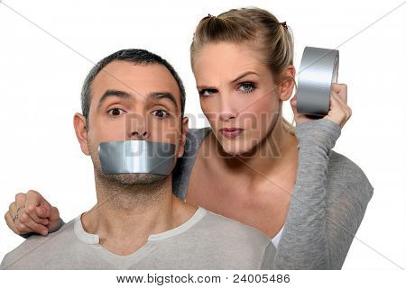 Woman taping-up mans mouth