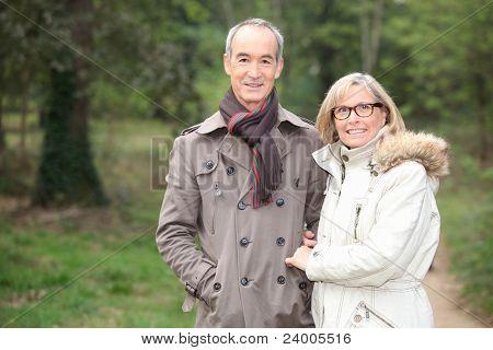 Elderly couple walking through woods