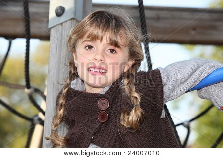 tired little blonde girl in a playground