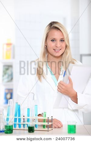 Young student with test tube rack and notes