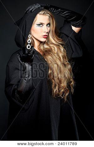 Encantadora bruja de halloween sobre fondo negro.