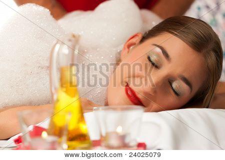 Wellness - woman getting massage in Spa; it is a massage with foam