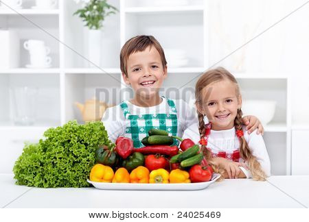 Happy healthy kids with vegetables in the kitchen - ready to prepare a meal