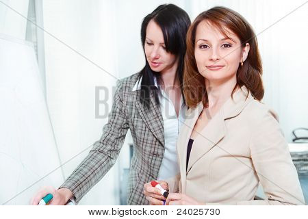 Businesswomen writing on the whiteboard