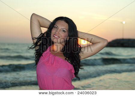 Atractivo modelo mujer en playa puesta del sol