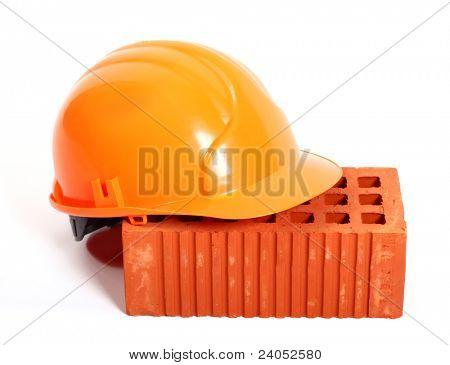 Perforated brick and orange hard hat isolated on white