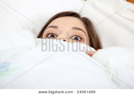 Scared young woman in bed.