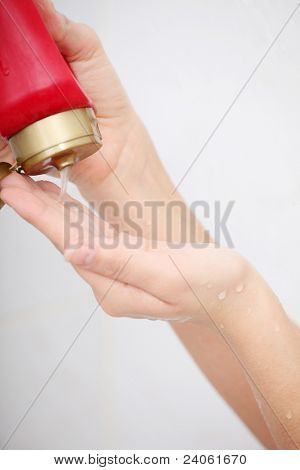 Liquid Gel Soap Pouring from Bottle into a Woman's Hand