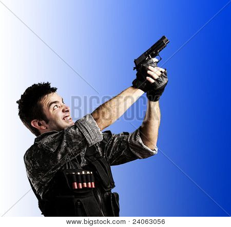 portrait of young soldier shooting with a gun against a white background