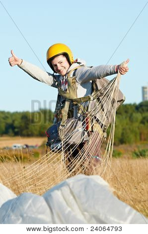 single Happy parachute jumper after landing at field and blue sky background