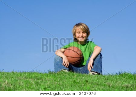 Happy Boy Resting With Basket Ball