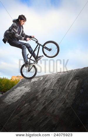 Jovem homem pulando e andando em uma bicicleta de BMX em uma rampa sobre fundo de céu azul