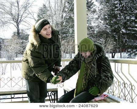 Lovers guy with a girl in a park gazebo in winter