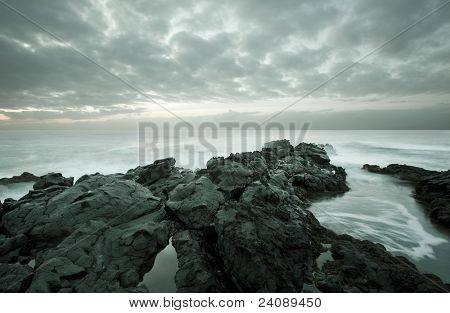 Tide coming in as blurred motion on a rocky beach during twilight