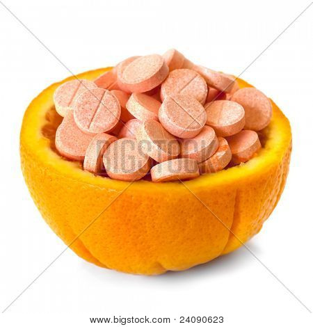 Vitamin C tablets piled in half an orange, isolated on white.