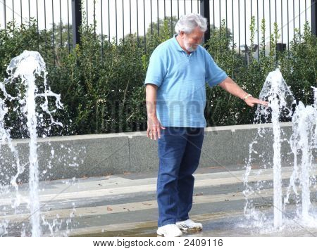 Senior Playing In The Water Fountain