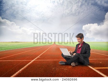 Smiling businessman sitting on a running track and using a laptop