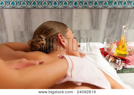 Wellness - woman getting massage in Spa; the therapist is using a glove