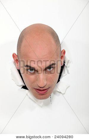 Un hombre calvo haciendo estallar a través de una pared.