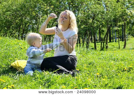 mother and child playing on green field