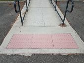 Red Cement Bumps And Cement Walkway With A Railing poster