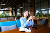 Woman Having Break At Cafe With Smartphone, Notebook And Drinking Coffee. Concept Of Having Break An poster