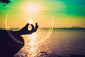 Silhouette, Hand Of Woman Meditating In Yoga Pose Or Lotus Position By The Sea At Sunset. Rear View. poster
