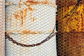 pic of chicken-wire  - Old rusty drums behind a chicken wire fence - JPG