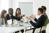 Diverse Employees Arguing During Team Meeting, African Office Worker Disagreeing With Caucasian Coll poster