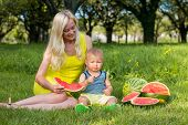Beautiful Young Mother And Little Son Are Sitting On The Grass And Eating A Watermelon. Picnic. Mom  poster
