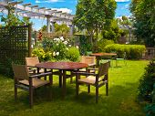 Landscaped Garden With Wooden Dining Table Set In The Shade Of Trees poster