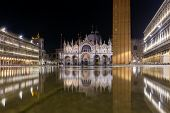 Basilica in San Marco square in Venice with reflection at night during the high tide, or aqua alta,  poster