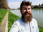 Man, Tourist With Beard And Mustache On Cheerful, Smiling Face, Riverside Background. Selfie Photo C poster