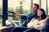 Cheerful couple watching TV together poster