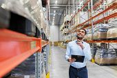 logistic business, shipment and people concept - happy businessman with clipboard at warehouse poster