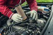 The Auto Mechanic Replaces The Cars Oil Filter. poster