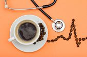 White Cup Of Coffee On Saucer With Coffee Beans Folded In The Form Of A Cardiogram And Phonendoscope poster