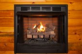 picture of retarded  - Lit electric fireplace built into log cabin wall - JPG