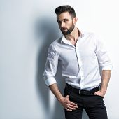 Handsome man in white shirt and black trousers - posing  at studio. Attractive guy with fashion hair poster