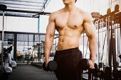 Muscular Bodybuilder Man Holding Rows Of Dumbbells Showing Muscular Body And Sixpack Abs At A Gym poster