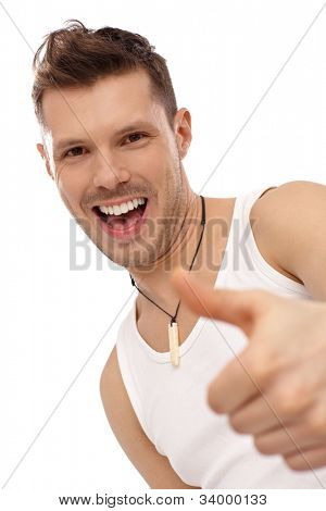 Portrait of successful happy young man showing thumb up, wearing undershirt. Yeah.