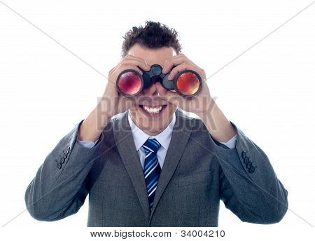 Smiling Businessman Looks Through Binoculars