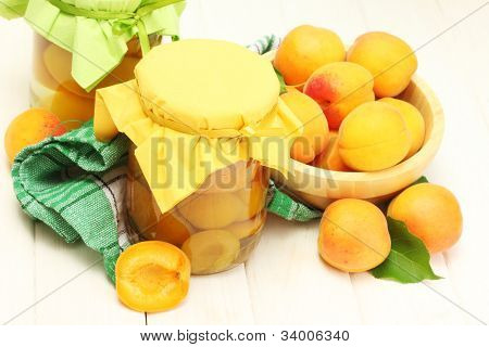 canned apricots in a jars and ripe apricots in bowl on white wooden table
