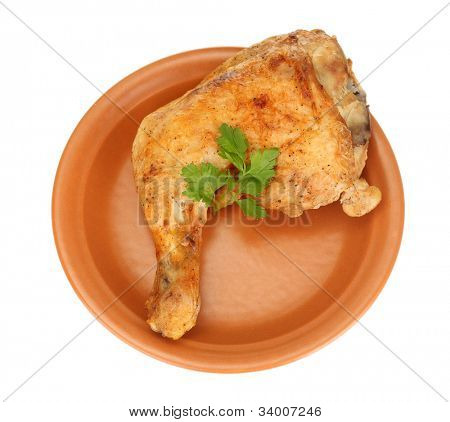 roasted chicken leg with parsley in the plate isolated on white