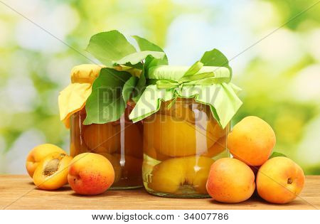 canned apricots in a jars and sweet apricots on wooden table on green background