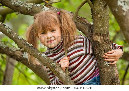lustige schöne Mädchen posiert auf einem Baum im Garten sitzen