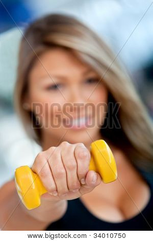 Woman at the gym lifting a free-weight and smiling